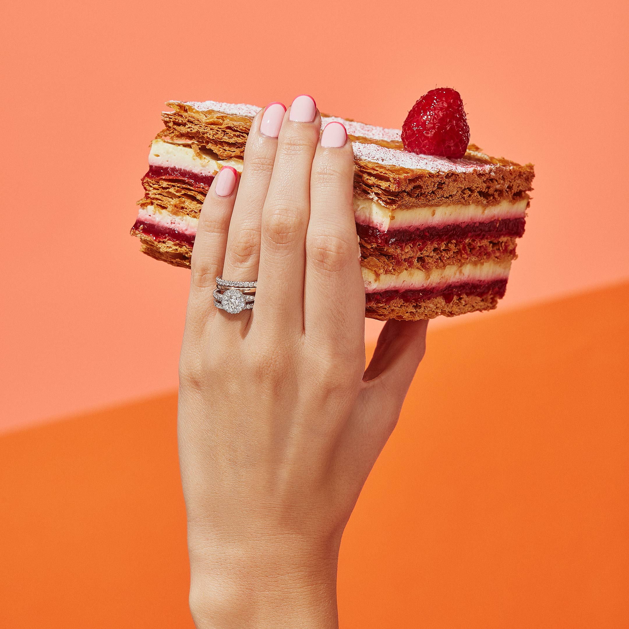 Camille Round Brilliant Seamless Halo® Engagement Ring with a twisted diamond pavé band in Platinum Hand with Cake Lifestyle by Oui by Jean Dousset