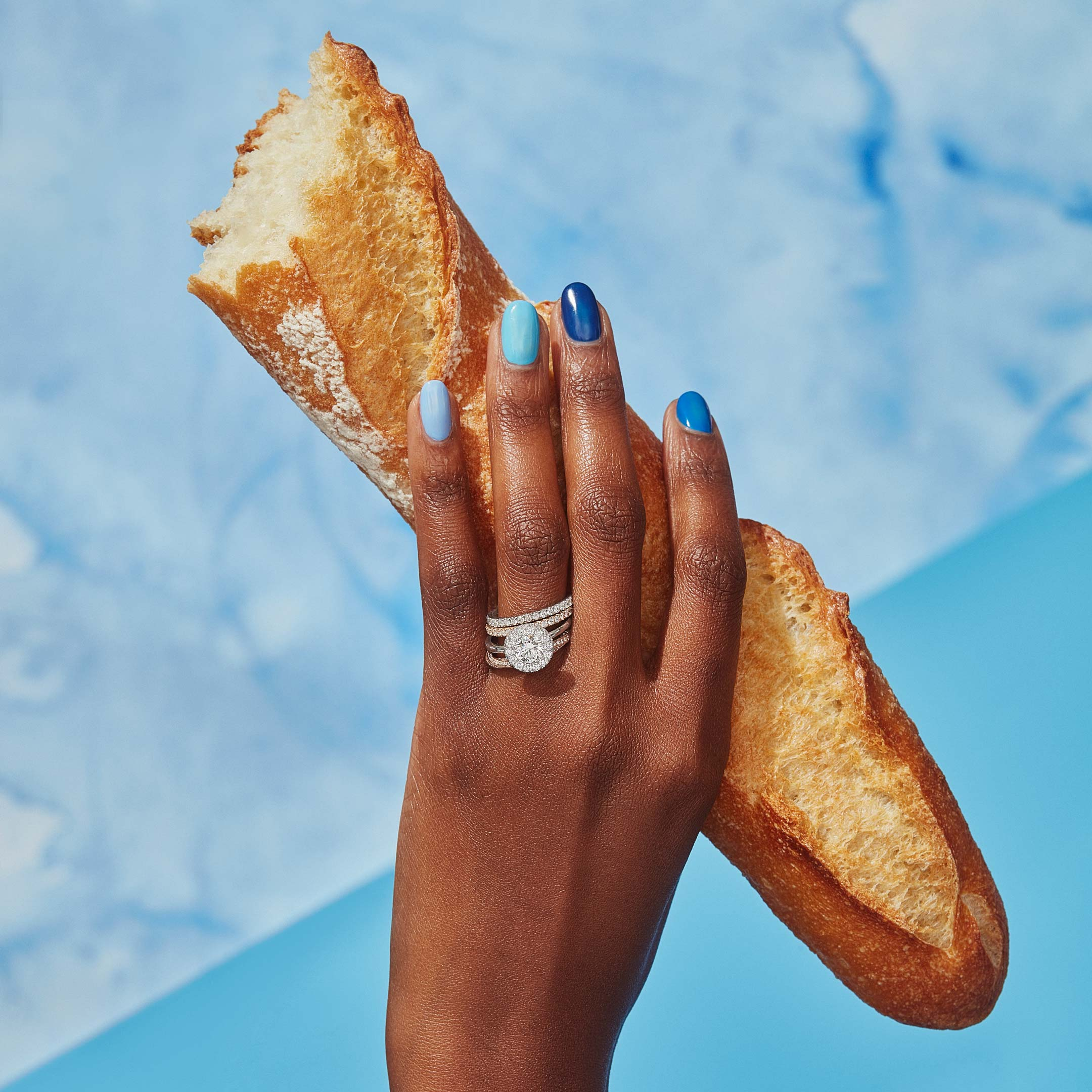 Colette Round Brilliant Seamless Halo® Engagement Ring with a solid band in Platinum Hand with Bread Lifestyle by Oui by Jean Dousset