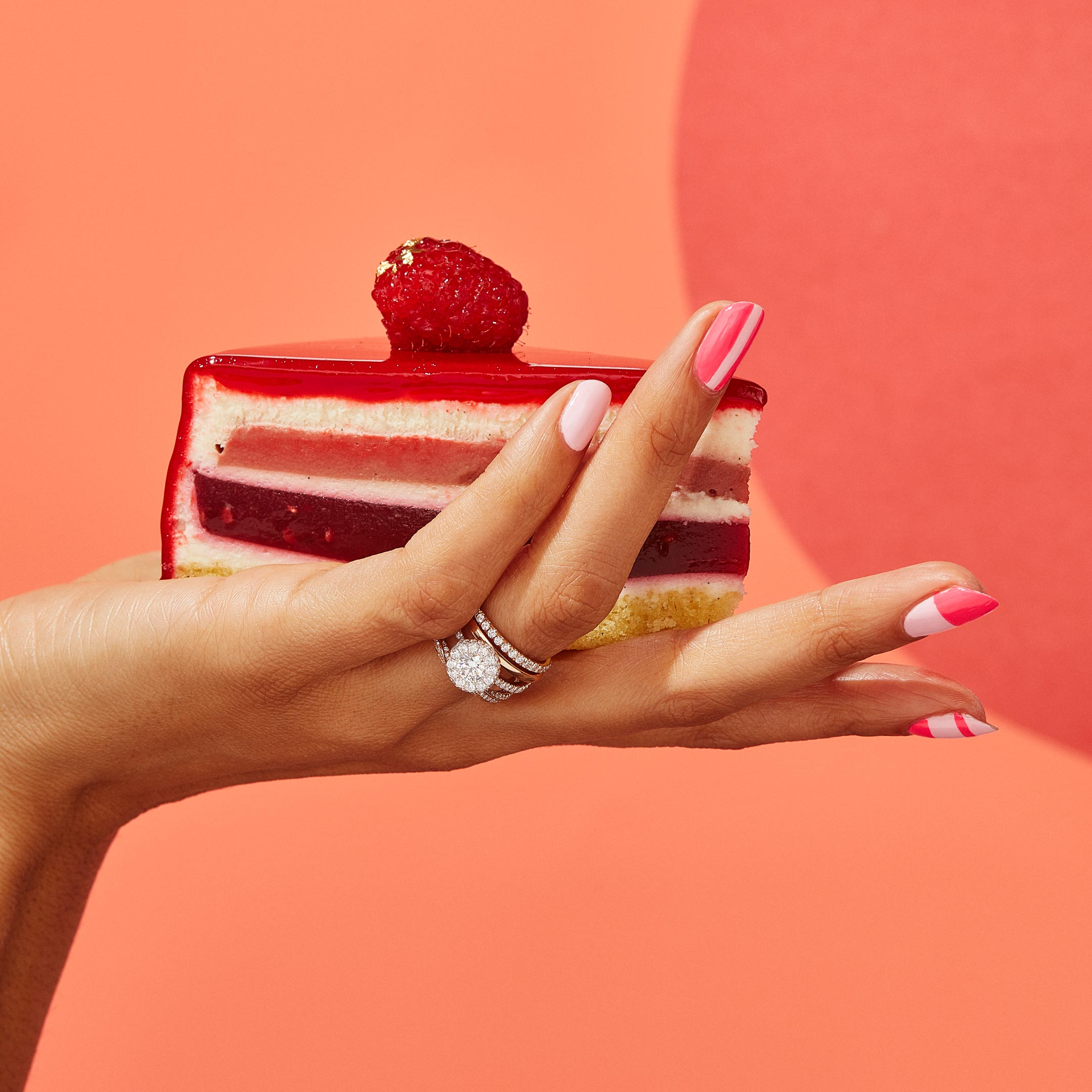 Eloise Round Brilliant Seamless Halo® Engagement Ring with a diamond pavé band in 18k Rose Gold Hand with Cake Lifestyle by Oui by Jean Dousset