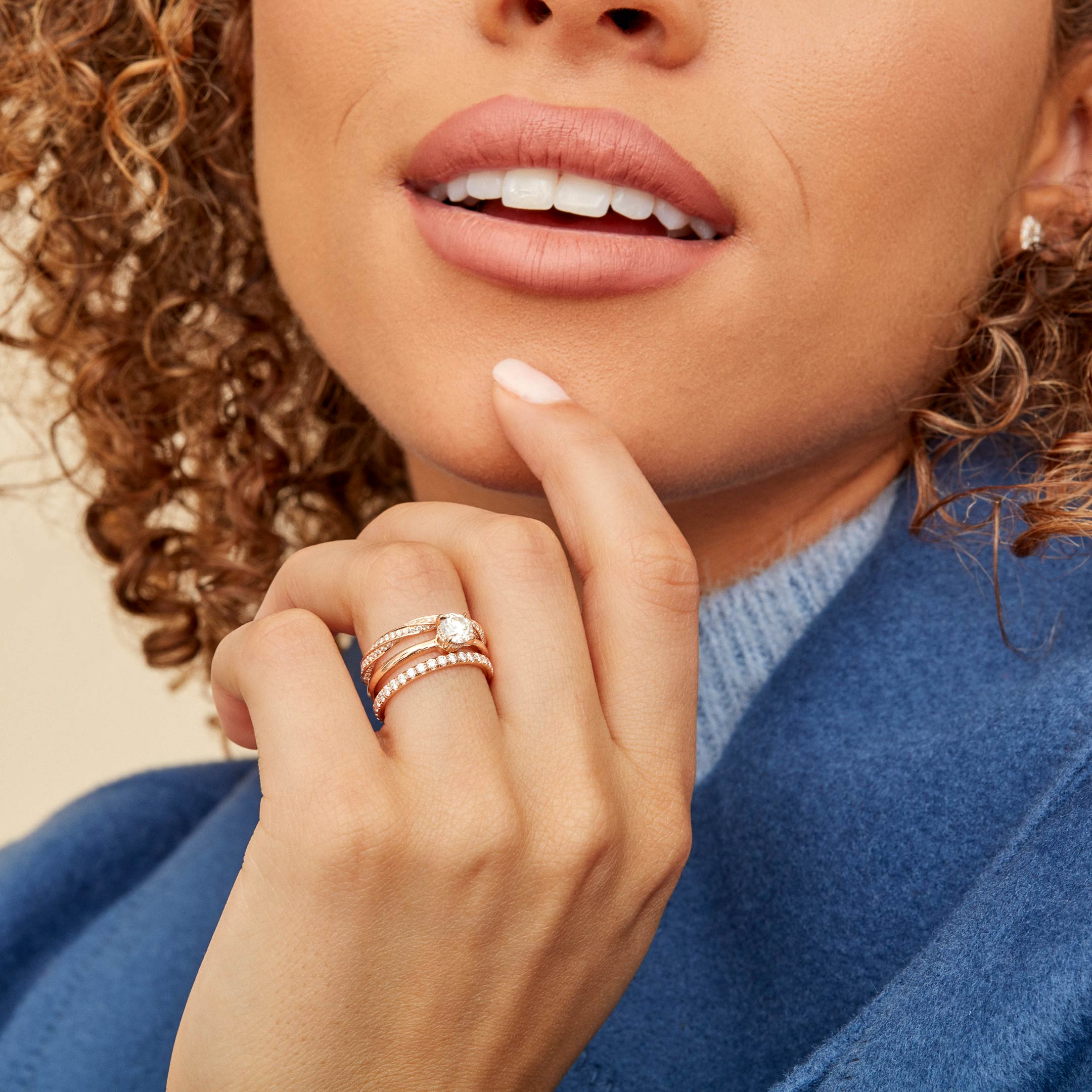Colette Round Brilliant Solitaire Engagement Ring with a solid band in 18k Rose Gold Hand Against Model Lifestyle by Oui by Jean Dousset