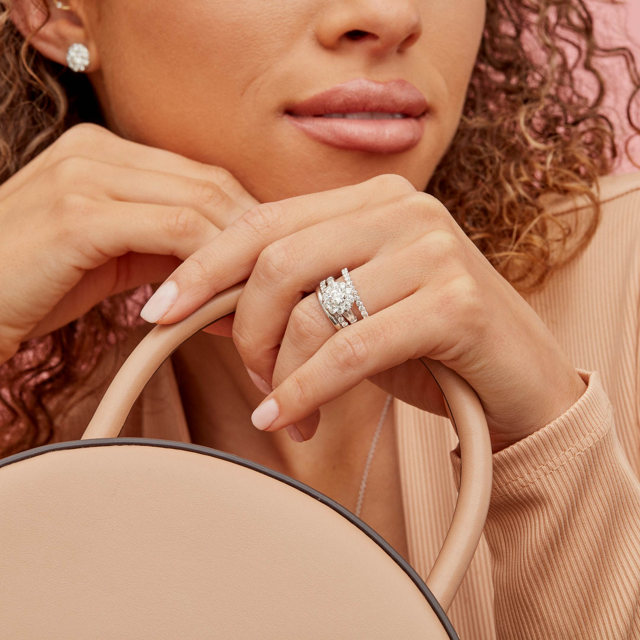 Madeline Round Brilliant Seamless Solitaire™ Three Stone Engagement Ring with tapered baguette side stones in Platinum Hand against Model Lifestyle by Oui by Jean Dousset