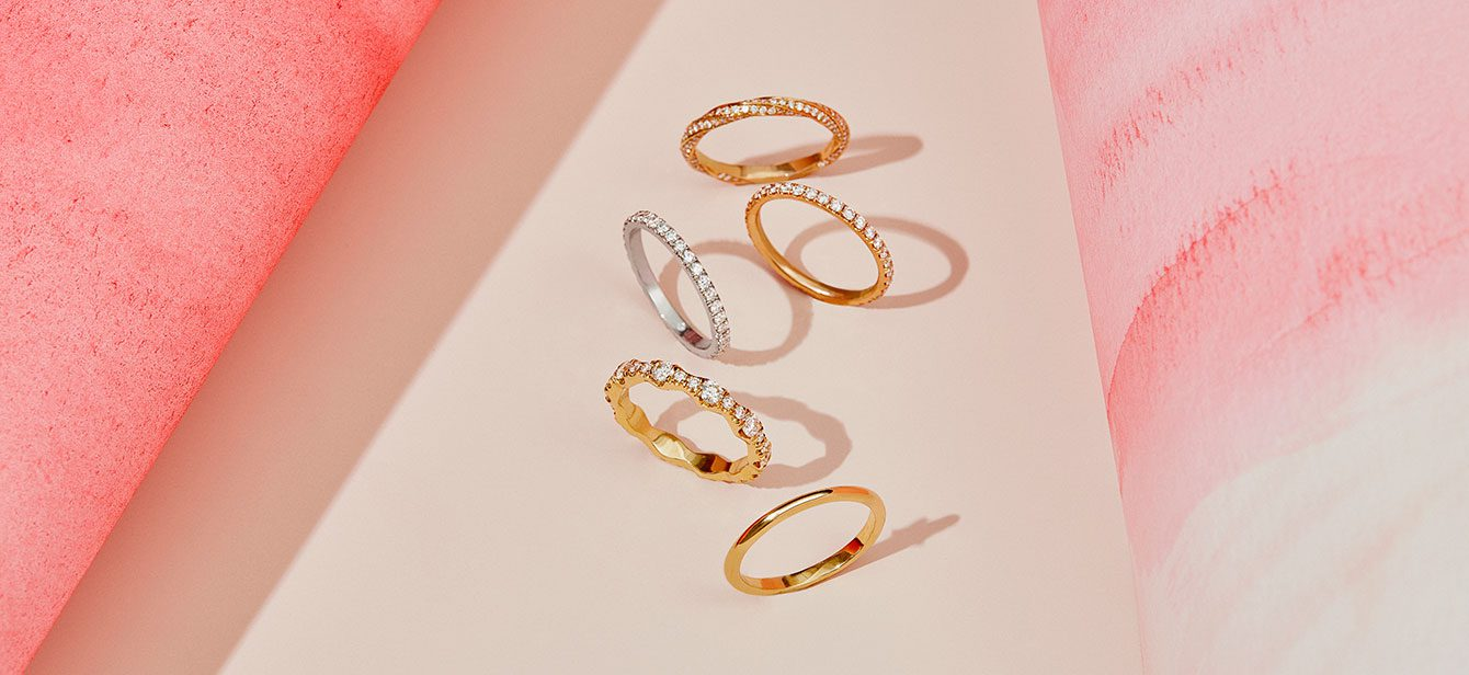 Women's Wedding Bands in Mixed Metals on Pink Background