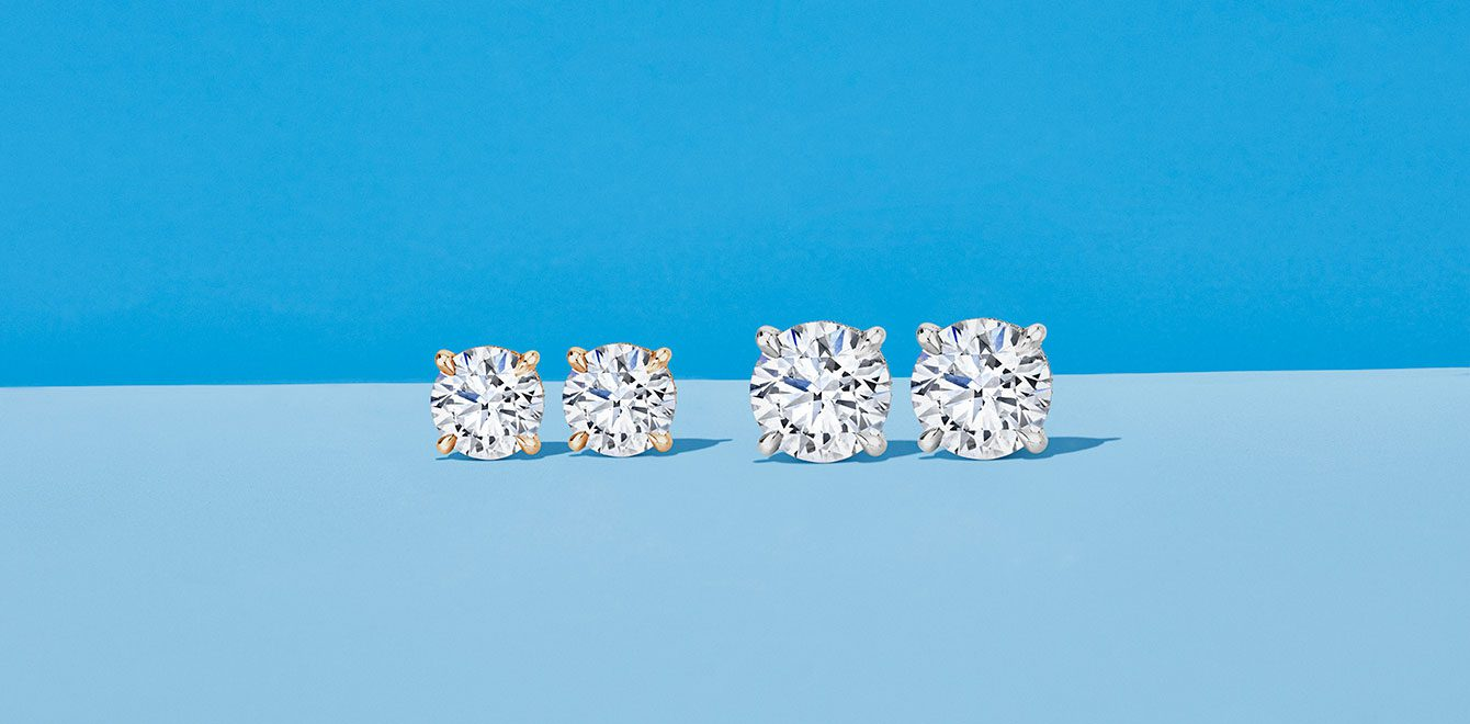 Two Pairs of Round Cut Lab Grown Diamond Earrings on Blue Background