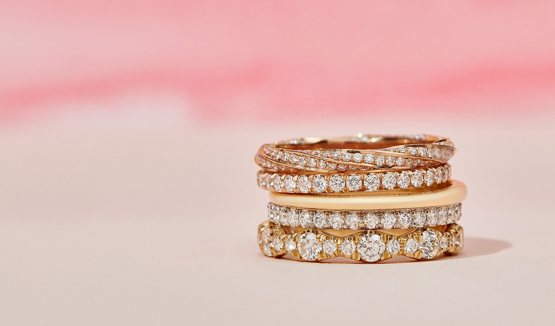 Women's Wedding Band Mixed Metals Product Stack on Pink Background
